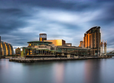 A panoramic photograph of Media City At Salford Quays, Greater Manchester, UK. Featuring a stormy moody sky.